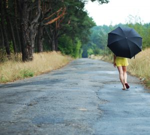 young woman with black umbrella walking in park on a rainy day